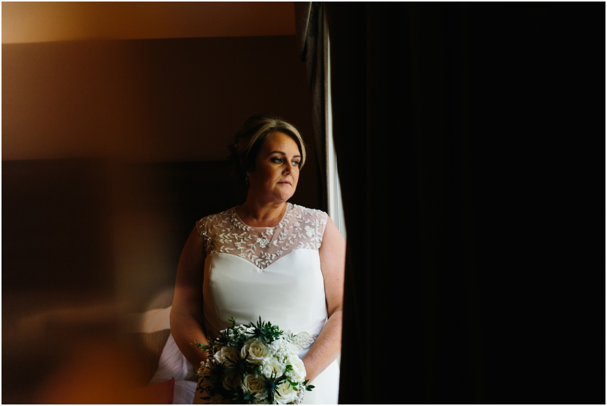 Bride in hotel room ready for her wedding day in beautiful dress